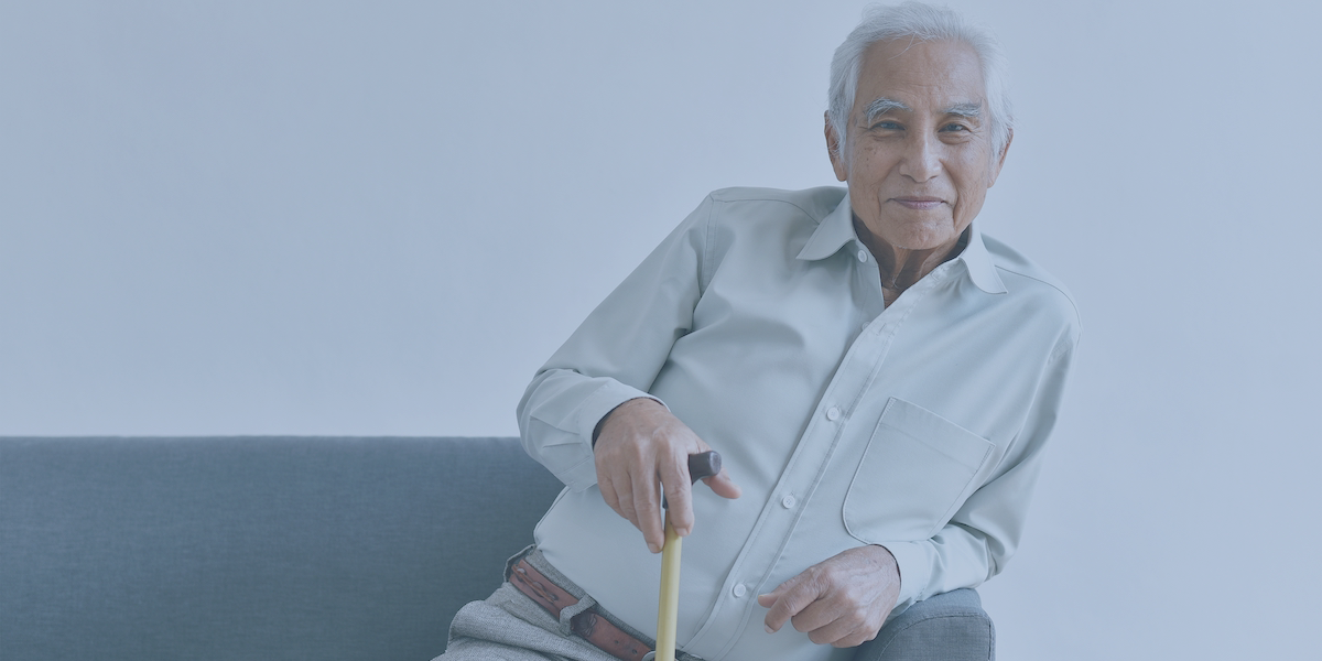 An elderly man holding a cane sits on a couch.