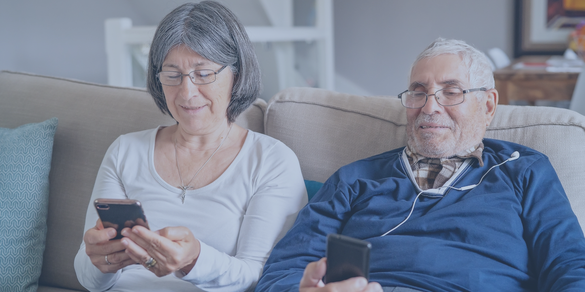 An old couple sitting on the couch each holding a smartphone.